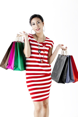 Woman in red stripes dress carrying shopping bags isolated on white photo