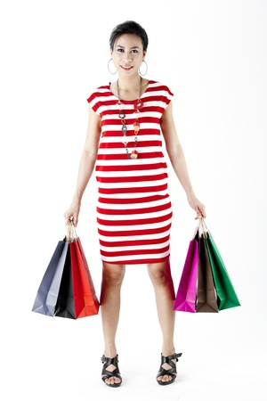Full length of woman in red stripes dress while carrying shopping bags isolated on white photo