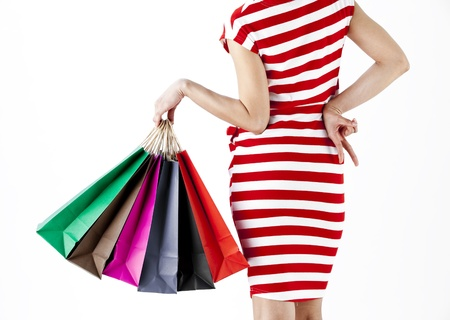 Woman in red stripes dress while carrying shopping bags with peace hand sign isolated on white Foto de archivo