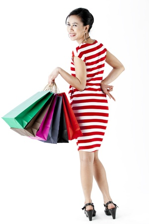 Full length of woman in red stripes dress while carrying shopping bags with peace hand sign isolated on white photo