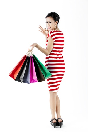 Full length of woman in red stripes dress while carrying shopping bags with okay hand sign isolated on white photo