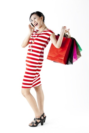 Full length of woman in red stripes dress on phone while carrying shopping bags isolated on white photo