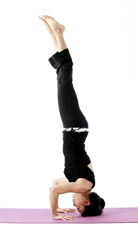 headstand: Asian female practising yoga in headstand pose