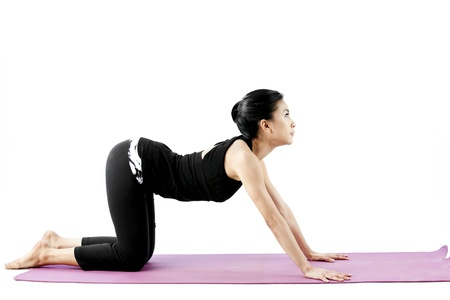 Asian female practising yoga in cow position photo