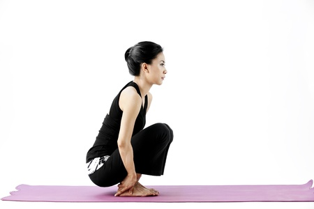 Asian female practising yoga while squatting on a mat