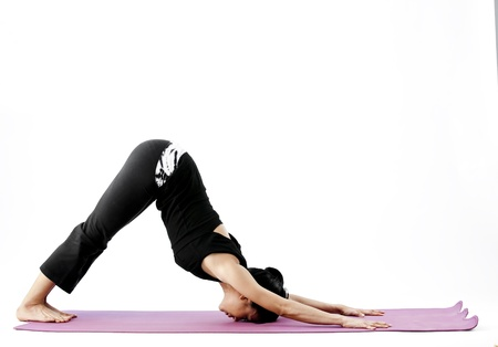 Asian female practising yoga in downward facing dog pose photo