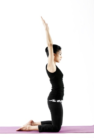 hand lifted: Asian female practising yoga while kneeling with arms lifted up