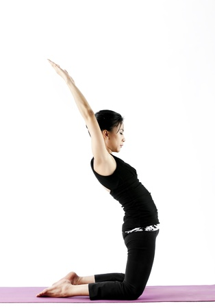 lifted: Asian female practising yoga while kneeling with arms lifted up