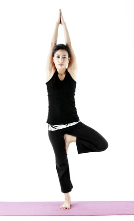 Extend: Asian female practising yoga in tree pose Stock Photo