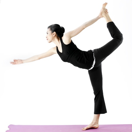 Asian female practising yoga in lord of the dance pose photo