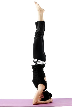 supported: Asian female practising yoga in supported headstand pose