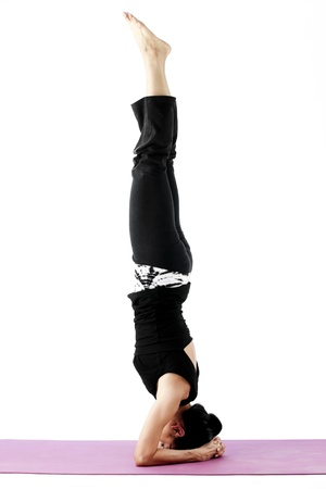 headstand: Asian female practising yoga in supported headstand pose
