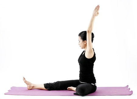 hand lifted: Asian female practising yoga on mat