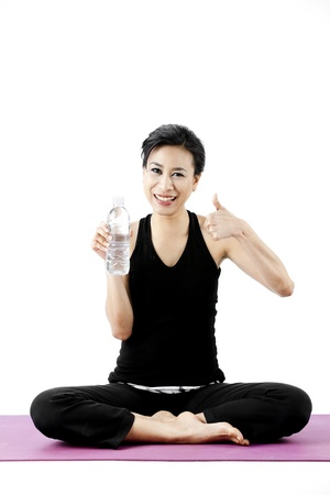 Asian female sitting legs crossed while posing with a water bottle and giving a thumbs up photo