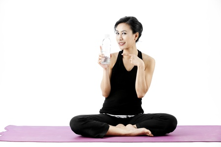 Asian female sitting legs crossed while pointing at a water bottle Stock Photo - 21854789