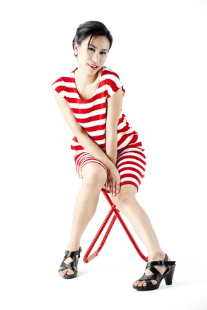 Asian woman in red stripes dress posing on a stool photo