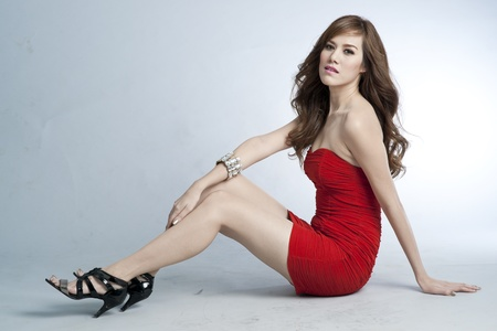 Sexy slim woman in red dress sitting on the floor photo