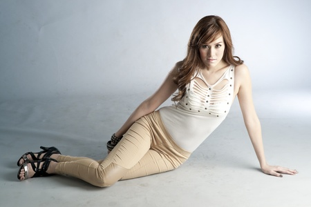 Sexy slim woman in fashionable attire sitting on the floor photo