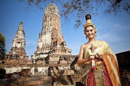 cultural history: Asian woman dressed in traditional Thai attire standing in front of a historical structure