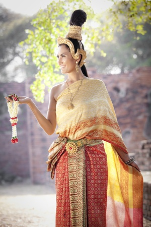 Asian woman dressed in traditional Thai clothing posing