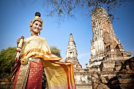 Asian woman dressed in traditional Thai attire standing in front of a historical structure