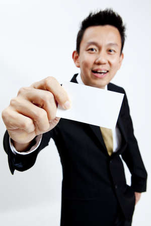 Businessman holding a blank business card isolated on white background photo
