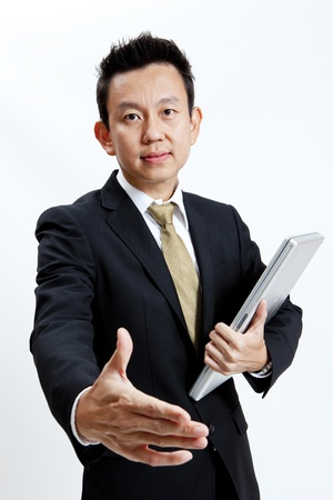 Businessman standing with laptop while offering handshake isolated on white background photo