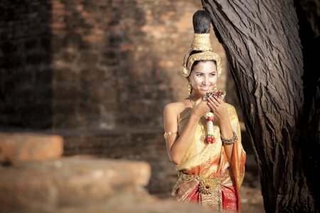 Thai woman is posing with her thai costume beside the tree photo
