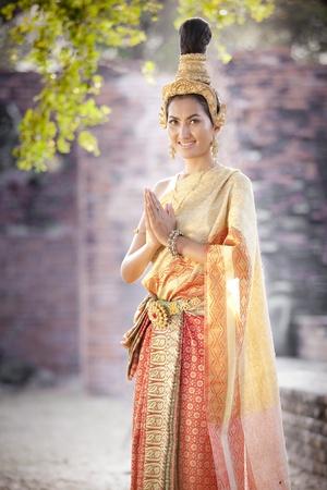 saluta: Thai donna in abito thai saluta con il tempio di sfondo tailandese