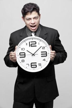 timeframe: A young businessman with analog clock on white background