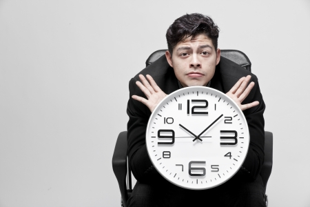 Close-up of a young businessman with analog clock photo