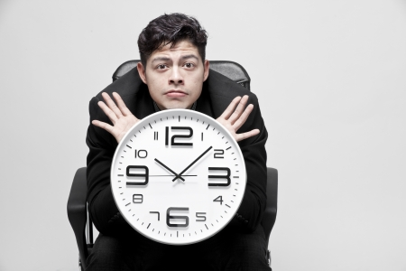 timezone: Close-up of a young businessman with analog clock Stock Photo