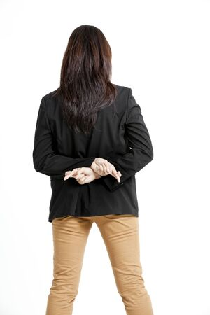 Young business woman with her fingers crossed behind her back isolated on white   background photo