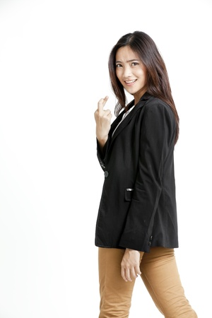 Young business woman with her finger crossed isolated on white background