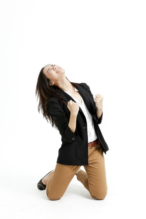 relieved: Young business woman kneeling down with her fists isolated on white background