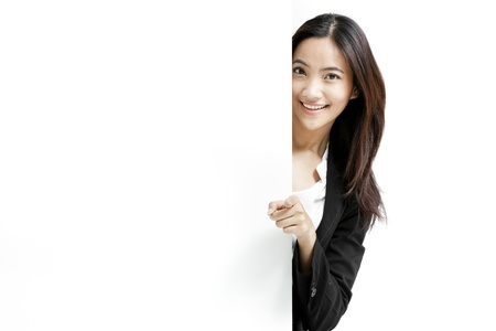 Young business woman posing next to a blank banner isolated on white background Stock Photo