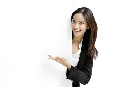 asian business people: Young business woman posing next to a blank banner isolated on white background Stock Photo
