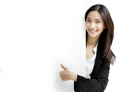 Young business woman posing next to a blank banner isolated on white background photo