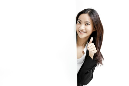 Young business woman posing next to a blank banner isolated on white background Foto de archivo