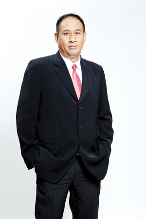 asian businessman: Mature businessman standing against white background with hands in pocket Stock Photo