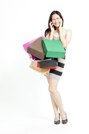 Pretty Asian woman in dress with shopping bags photo