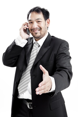 Businessman in suit on the phone offering handshake photo