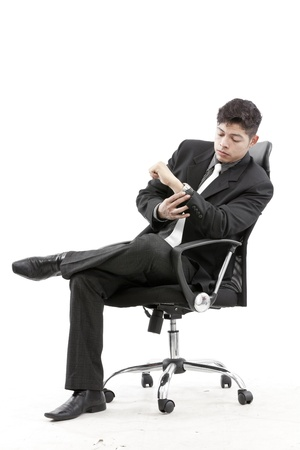 Businessman sitting and looking at watch photo