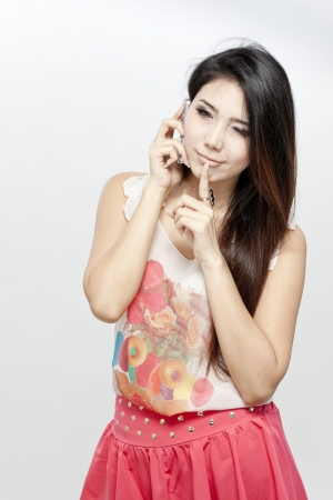 Asian woman on the phone with finger on lips photo
