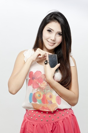Asian woman in blouse and pink skirt holding a smartphone photo