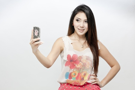 Asian woman taking a picture of herself with smartphone photo
