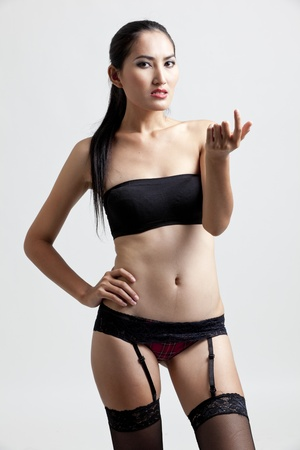 Sexy woman in black gesturing with hand photo