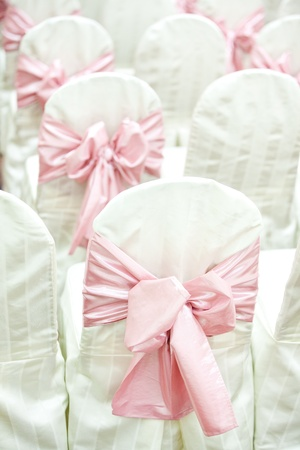 wedding chairs: Side view of pink ribbons on wedding chairs