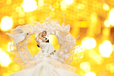Close up of bride and groom on top of a wedding cake photo