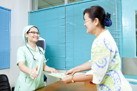 Nurse handing pamphlet to a patient photo